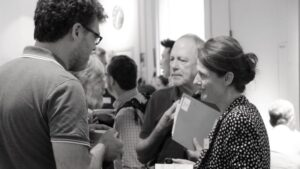 People speaking to each other in an event in black and white